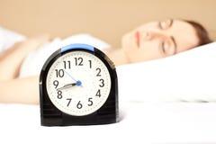 Mujer que duerme en la cama (foco en el reloj de alarma) Fotos de archivo libres de regalías