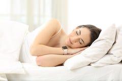 Mujer que duerme en la cama que lleva un smartwatch Imagen de archivo