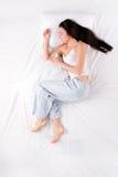 Mujer que duerme en la posición fetal abierta con la almohada Foto de archivo
