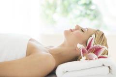 Mujer que duerme en la tabla del masaje en balneario de la salud Foto de archivo libre de regalías