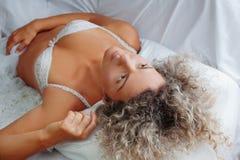 Mujer que duerme en su cama en el país Imagenes de archivo
