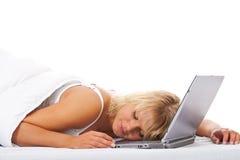 Mujer que duerme en su ordenador portátil en cama Foto de archivo