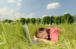Mujer que duerme en una computadora portátil Imágenes de archivo libres de regalías
