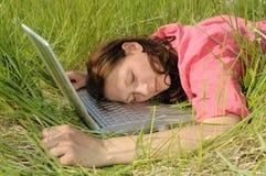 Mujer que duerme en una computadora portátil Foto de archivo libre de regalías