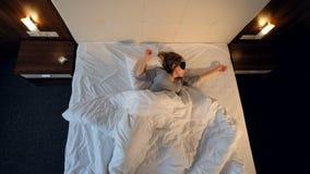 Mujer que duerme, lanzando y dando vuelta en cama 4K almacen de metraje de vídeo