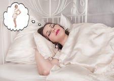 Mujer que duerme y que sueña sobre delgado ella misma del tamaño extra grande Foto de archivo libre de regalías