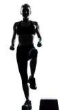 Mujer que ejercita aeróbicos del paso de progresión Imagen de archivo