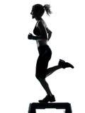 Mujer que ejercita aeróbicos del paso de progresión Fotografía de archivo libre de regalías