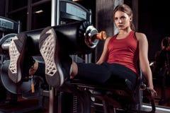 Mujer que ejercita con la cruce en piernas del entrenamiento del club de fitness o del gimnasio imagenes de archivo