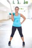 Mujer que ejercita con la pesa de gimnasia para su bíceps, al aire libre Imagen de archivo