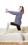 Mujer que ejercita con música que escucha de las pesas de gimnasia Fotografía de archivo