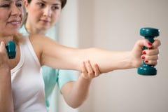 Mujer que ejercita con pesas de gimnasia Foto de archivo libre de regalías