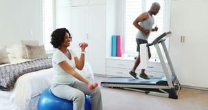 Mujer que ejercita con pesas de gimnasia mientras que hombre que activa en la rueda de ardilla 4k almacen de metraje de vídeo