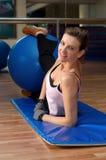 Mujer que ejercita con una bola del ejercicio de Pilates Fotografía de archivo libre de regalías