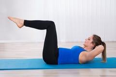Mujer que ejercita en clase de la yoga fotografía de archivo libre de regalías