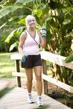 Mujer que ejercita en el parque que recorre con los pesos de la mano Fotografía de archivo libre de regalías
