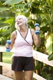 Mujer que ejercita en el parque que recorre con los pesos de la mano Fotos de archivo libres de regalías