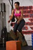 Mujer que ejercita en el salto en el gimnasio Fotografía de archivo