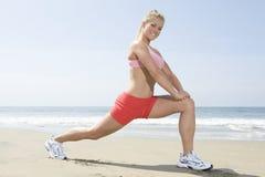 Mujer que ejercita en la playa Imagen de archivo