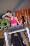 Mujer que ejercita en la rueda de ardilla en gimnasio Imágenes de archivo libres de regalías