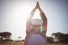 Mujer que ejercita mientras que usa los vidrios de la realidad virtual contra el cielo azul Fotografía de archivo libre de regalías