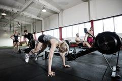 Mujer que ejercita por el aparato de remar en gimnasio Imagen de archivo
