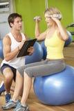 Mujer que ejercita ser animado por el instructor personal In Gym foto de archivo