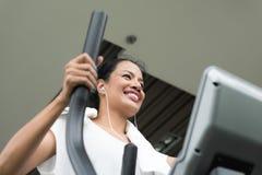 Mujer que ejercita y que se resuelve en gimnasio de la aptitud Fotografía de archivo libre de regalías