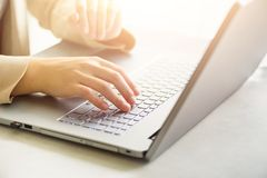 Mujer que elabora en cierre del ordenador La mujer da mecanografiar en el teclado del ordenador portátil, detalle en línea de las imagen de archivo