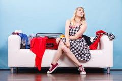 Mujer que elige cosas para embalar en la maleta Fotografía de archivo