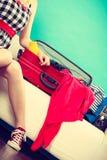 Mujer que elige cosas para embalar en la maleta Fotografía de archivo libre de regalías