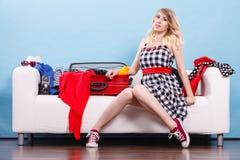 Mujer que elige cosas para embalar en la maleta Imagen de archivo libre de regalías