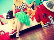 Mujer que elige cosas para embalar en la maleta Imágenes de archivo libres de regalías