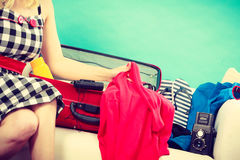 Mujer que elige cosas para embalar en la maleta Fotos de archivo libres de regalías