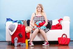 Mujer que elige cosas para embalar en la maleta Foto de archivo