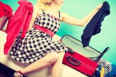 Mujer que elige cosas para embalar en la maleta Fotos de archivo