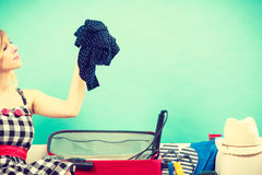 Mujer que elige cosas para embalar en la maleta Imagen de archivo