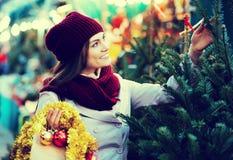 Mujer que elige el árbol del Año Nuevo Fotografía de archivo libre de regalías