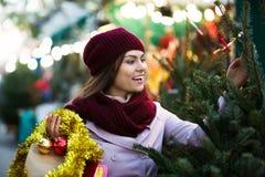 Mujer que elige el árbol del Año Nuevo Imágenes de archivo libres de regalías