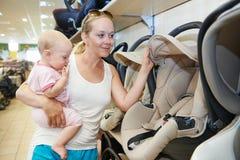 Mujer que elige el asiento de carro del niño foto de archivo