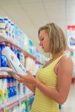 Mujer que elige el detergente Imagen de archivo libre de regalías