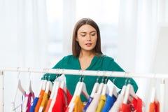 Mujer que elige el guardarropa de la ropa en casa Fotografía de archivo libre de regalías