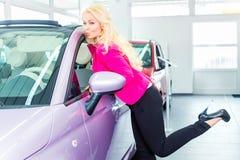 Mujer que elige el nuevo coche en la representación fotos de archivo