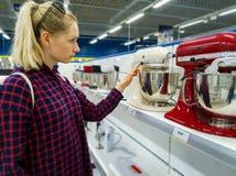 Mujer que elige el nuevo mezclador de la cocina en tienda de los aparatos electrodomésticos fotografía de archivo libre de regalías