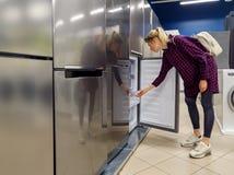 mujer que elige el nuevo refrigerador en tienda de los aparatos electrodomésticos fotos de archivo