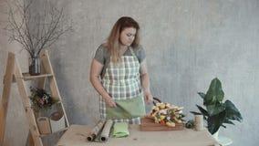 Mujer que elige el papel de Kraft para el arreglo comestible metrajes