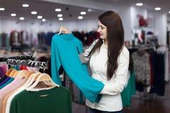 Mujer que elige el suéter en la tienda de la ropa Imagen de archivo libre de regalías