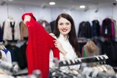 Mujer que elige el suéter en la tienda de ropa Fotos de archivo libres de regalías