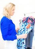 Mujer que elige el vestido Fotos de archivo