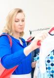 Mujer que elige el vestido Fotos de archivo libres de regalías